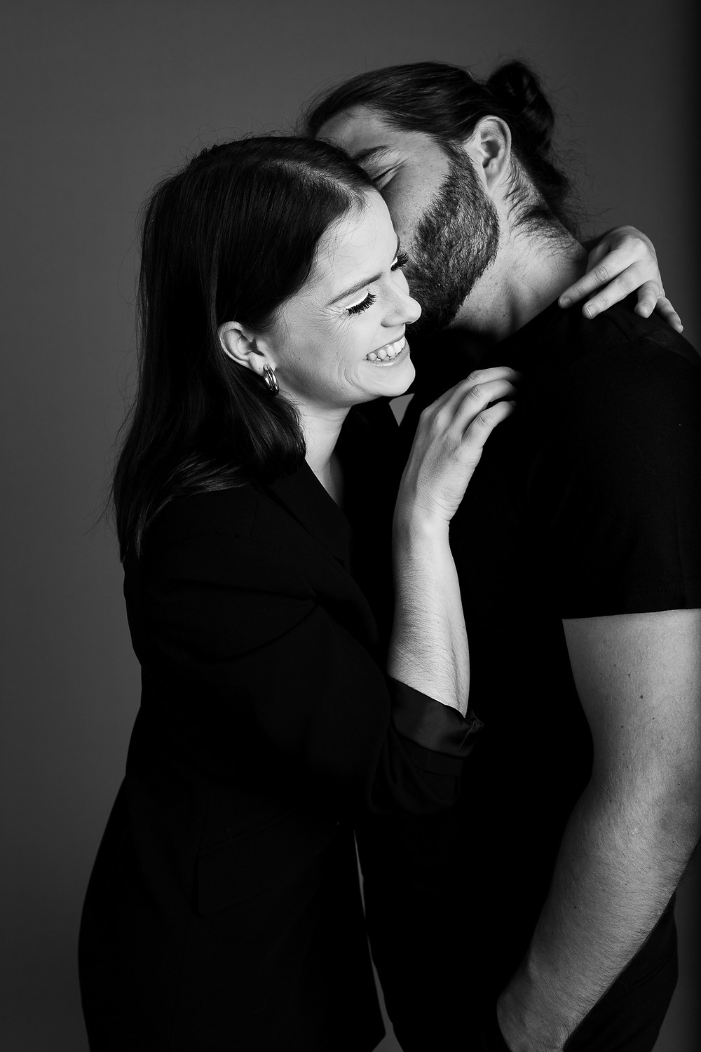black and white image of man kissing his girlfriend's cheek