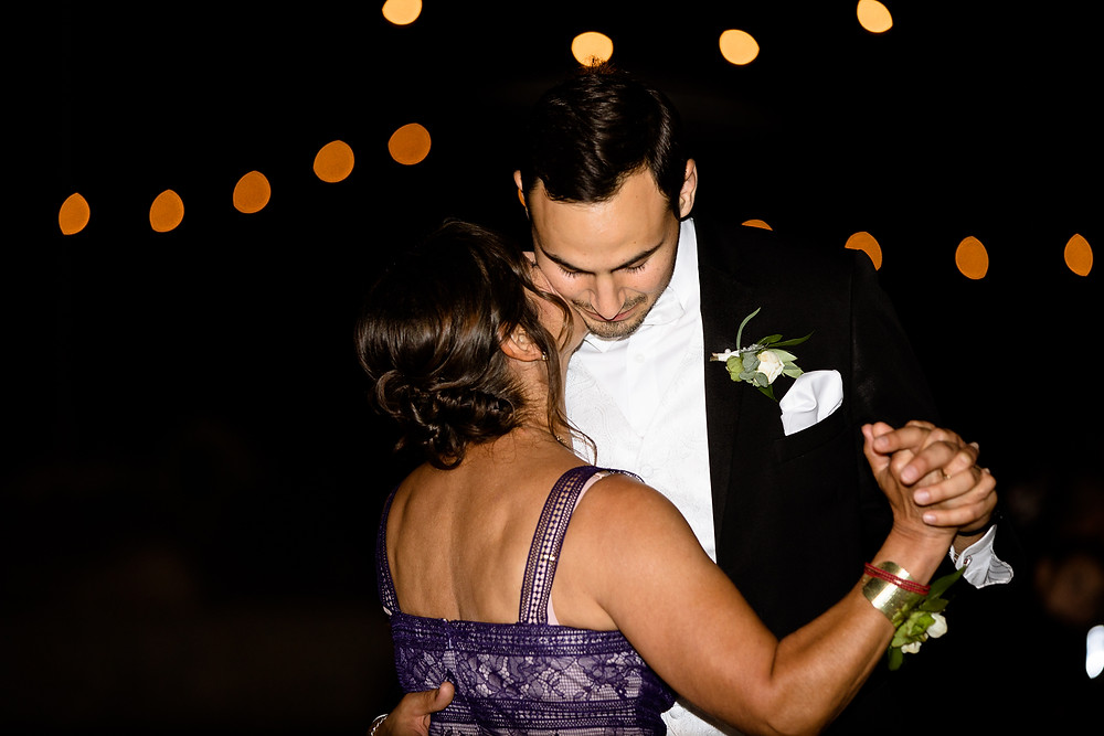 mother of the groom kissing her son's cheek while they dance