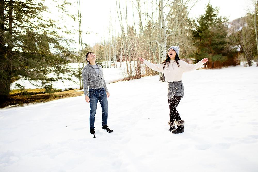 man and woman smiling at snow falling in park city, utah