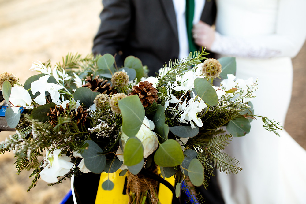 bridal bouquet made of pine cones, thistle, eucalyptus, and pine