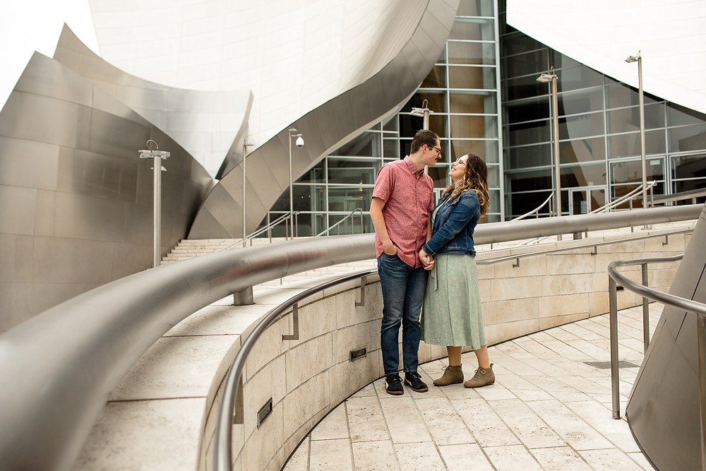 man and woman holding hands on ramp in front of walt disney concert hall in dtla