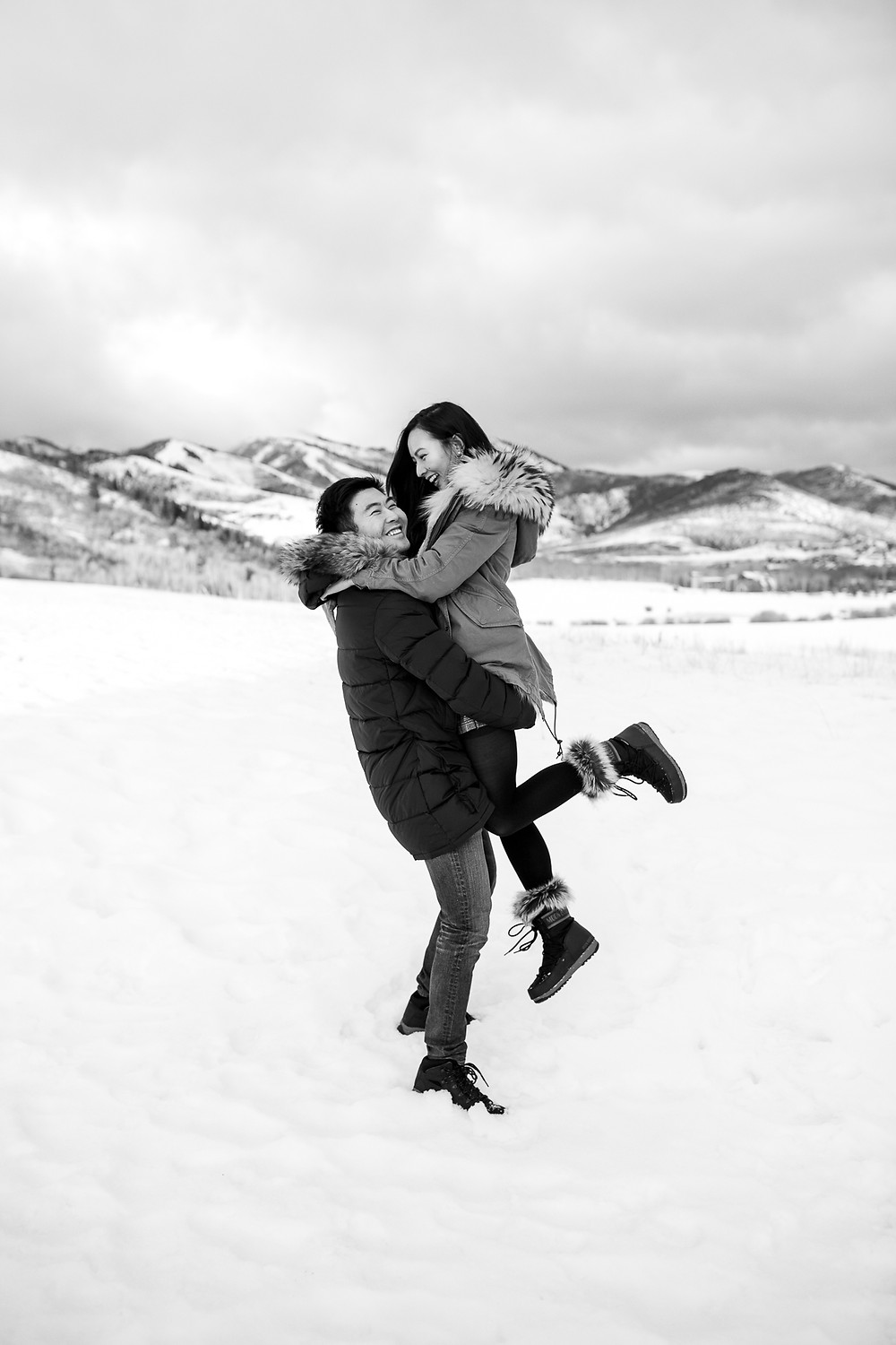 black and white photo of couple spinning and smiling