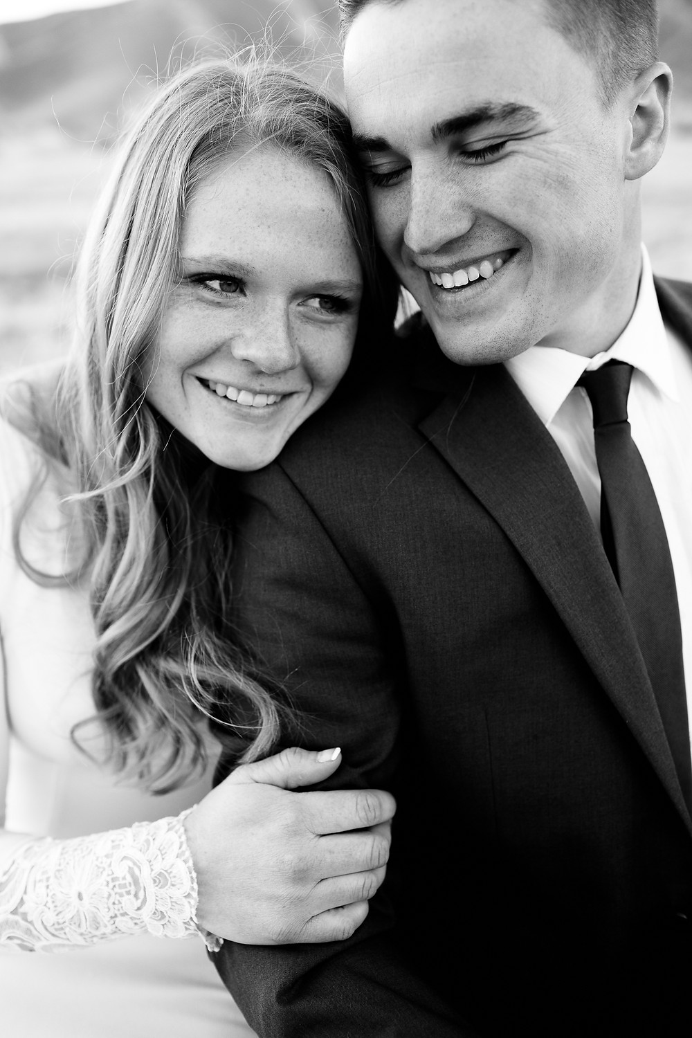 bride and groom smiling at each other in black and white