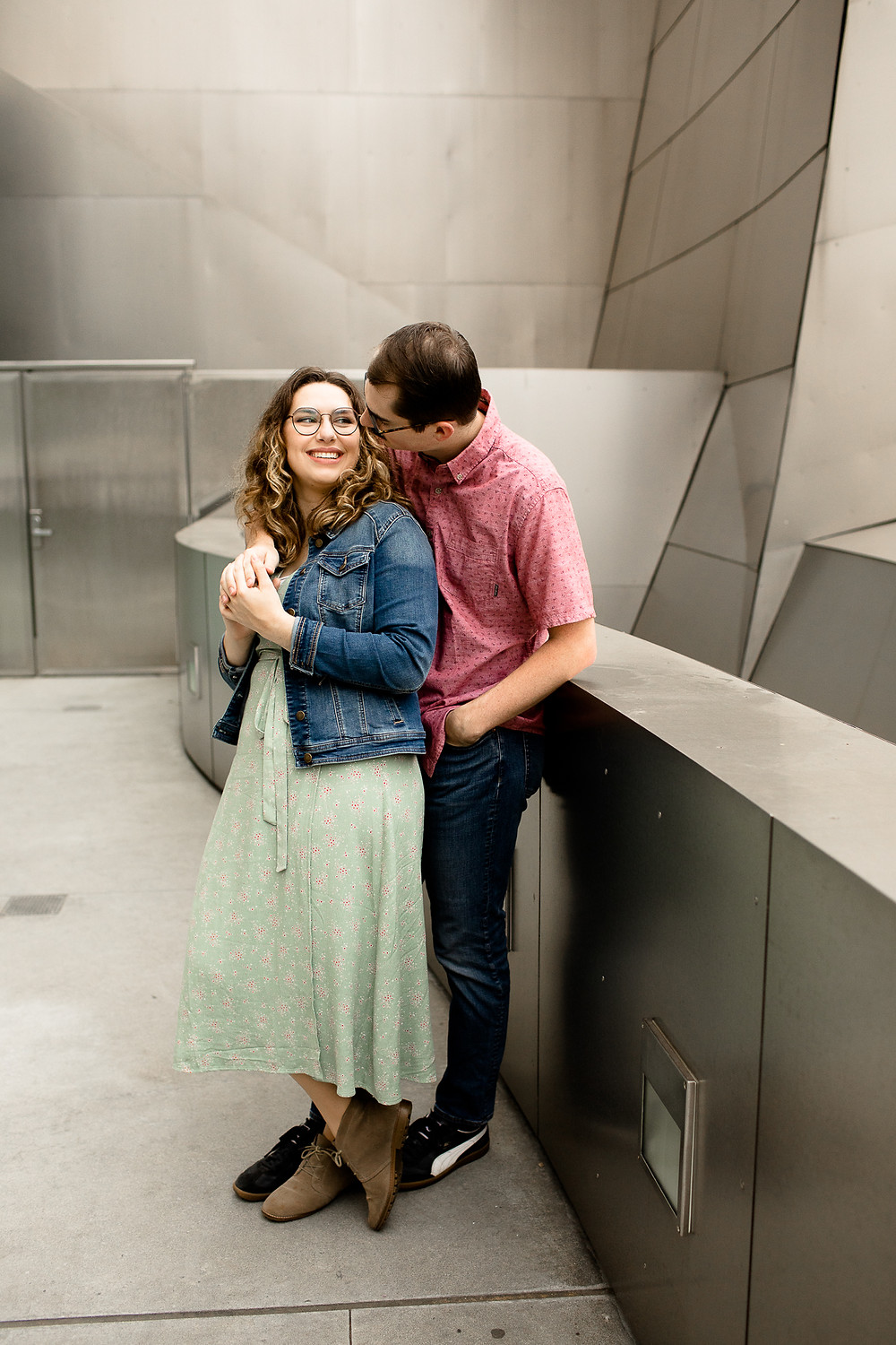 man hugging woman in engagement photos from behind in downtown los angeles