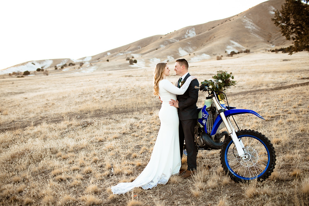 bride and groom leaning up against a dirtbike in the utah foothills