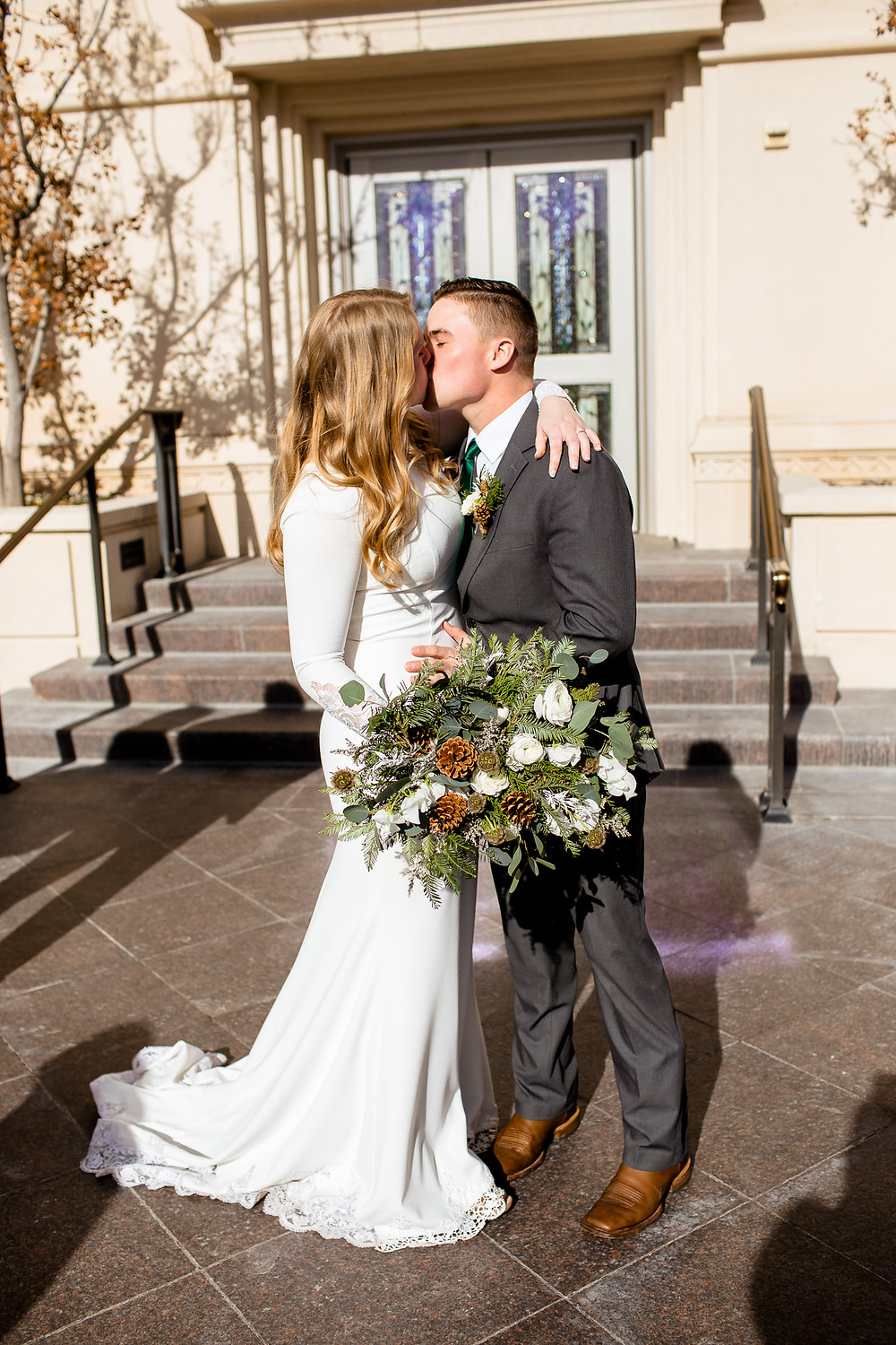 bride and groom kiss outside of payson, utah temple