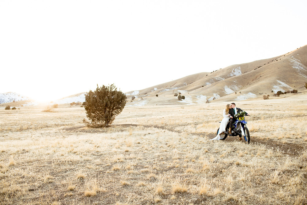 bride and groom kissing while sitting on a dirtbike in payson, utah foothills