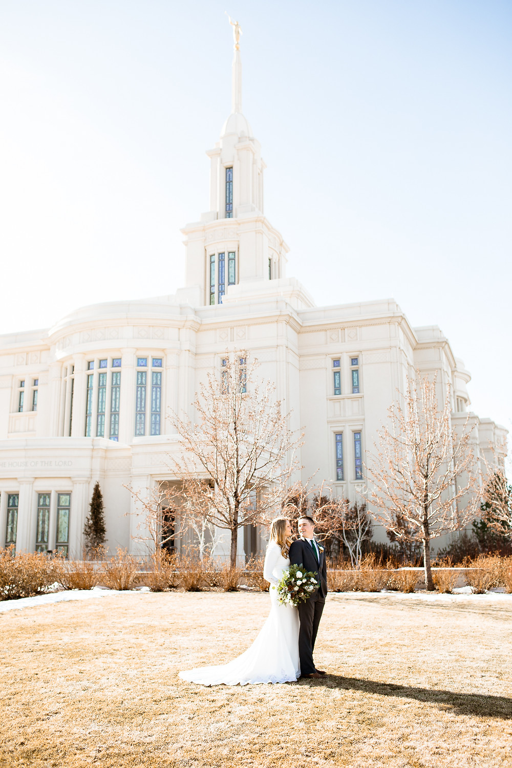 bride and groom smiling at each other on payson, utah temple lawn