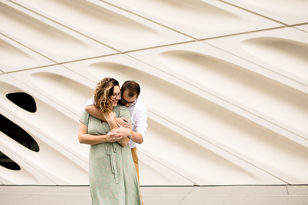 cute couple cuddling in front of the broad museum in downtown los angeles