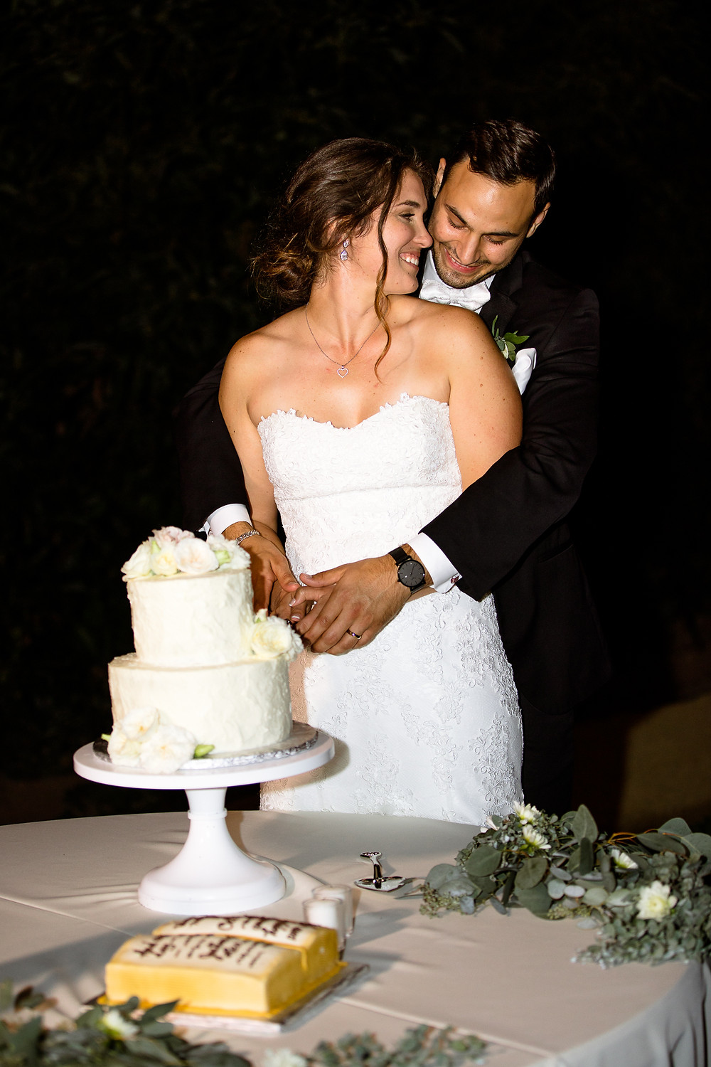 bride and groom giggling while cutting their cake