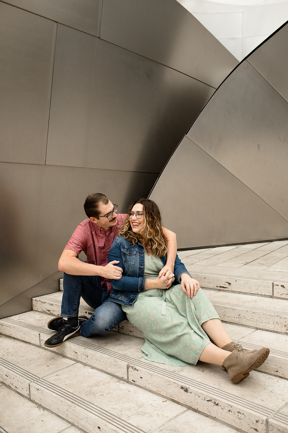 cute couple's engagement photos in front of walt disney concert hall, man and woman sitting down and cuddling