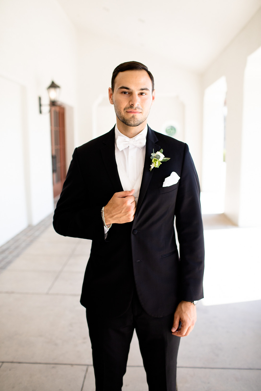 groom portrait in all-white entryway