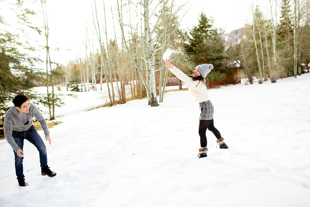 woman throwing snow at a man
