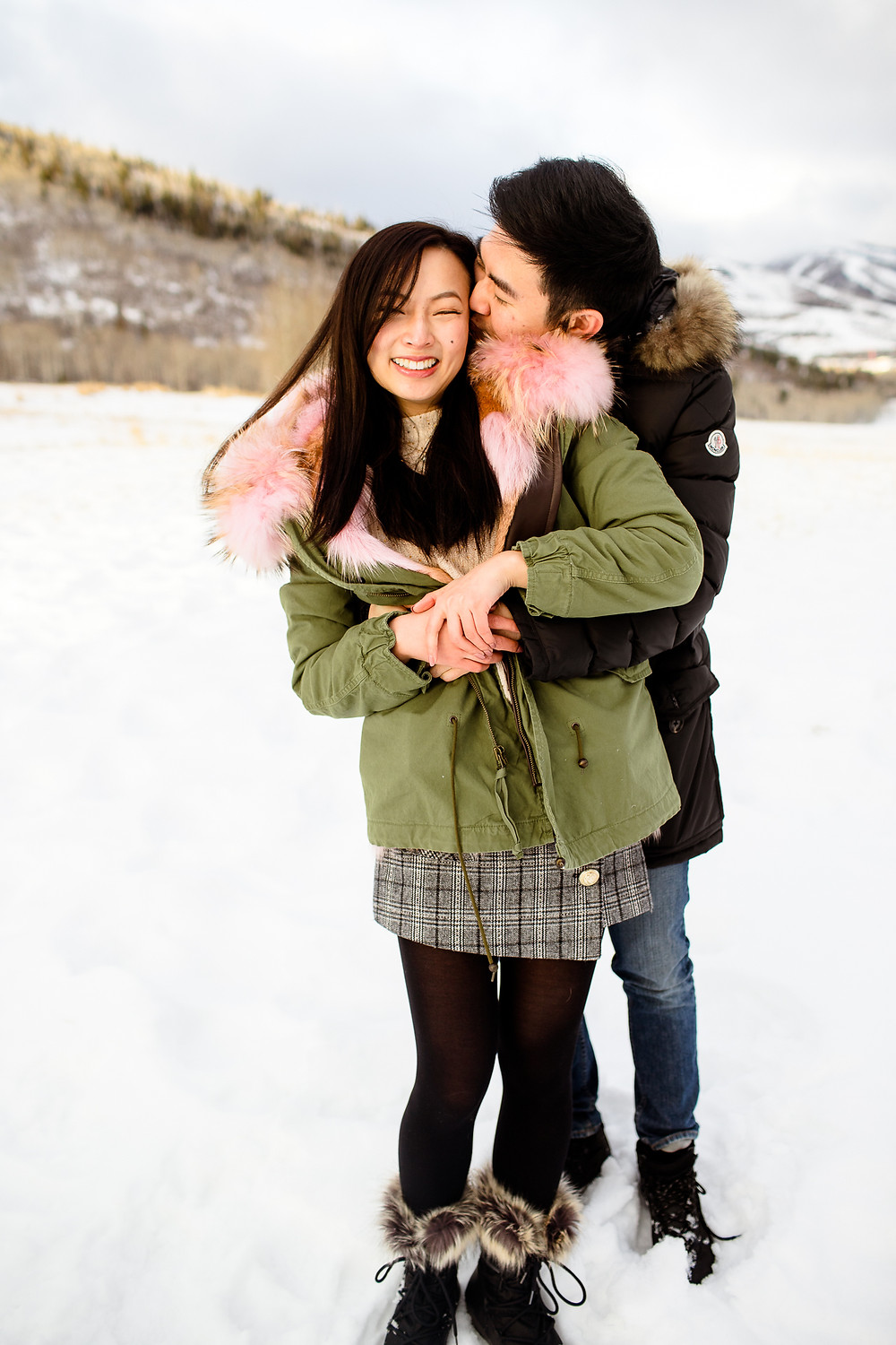 man kisses woman's cheek while hugging her from behind