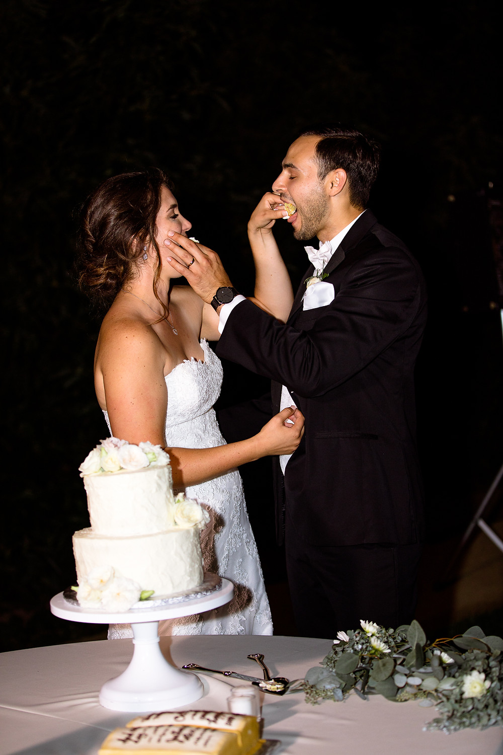 bride and groom feed each other a piece of their wedding cake