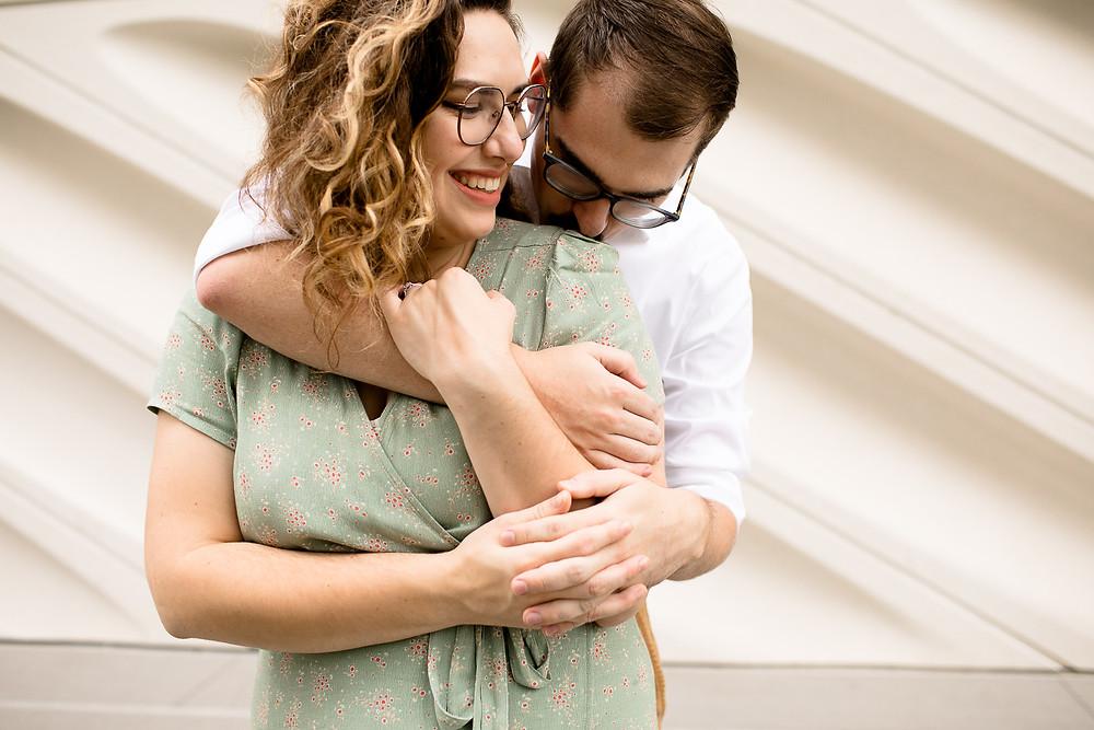 woman smiling while man kisses her shoulder in dtla