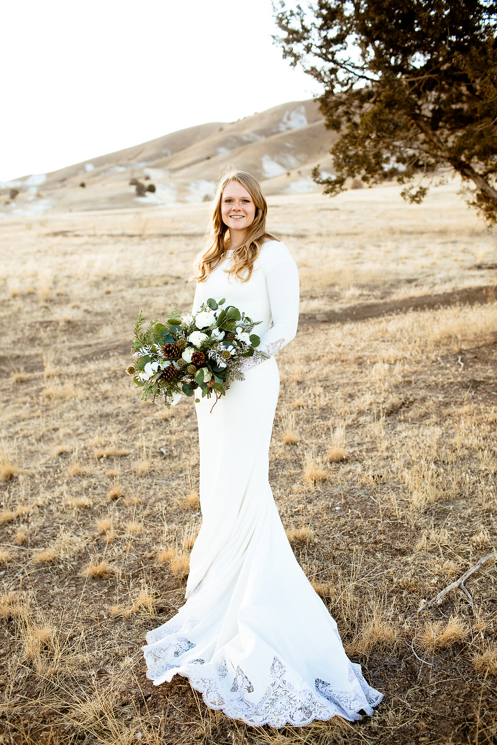 bride smiling at the camera while holding bouquet in payson utah foothills