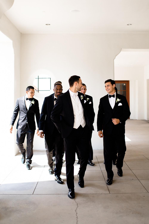 groomsmen in all black tuxes laughing at santa barbara ritz carlton
