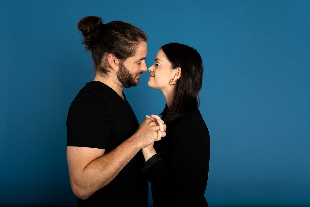 man and woman in black shirts holding hands and nuzzling noses against blue backdrop
