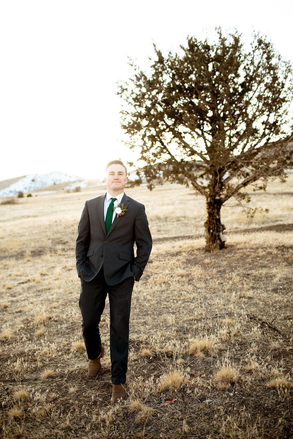 groom walking towards the camera in front of a tree