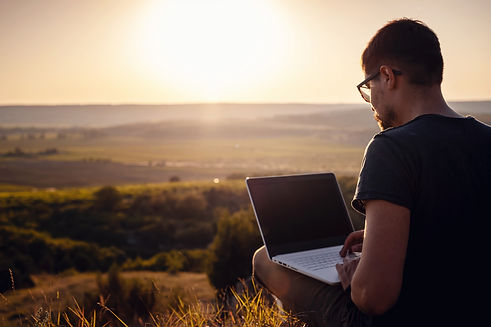 man with laptop sitting on the edge of a