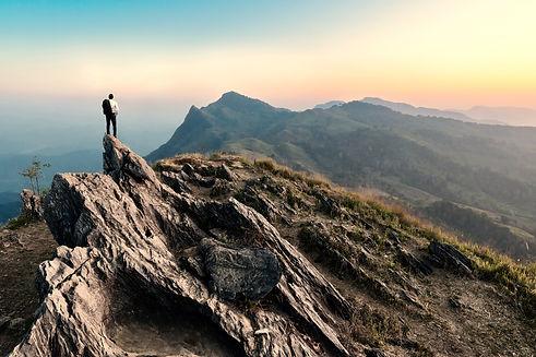 businessman hike on the peak of rocks mo