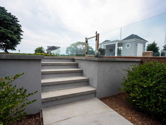 """Concrete poured retaining wall finished in a light gray stucco. The treads and capping stones are done in in ¾"""" porcelain bluestone with a 2"""" mitered edge."""