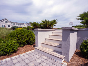 """The treads and capping stones are done in the same ¾"""" porcelain bluestone with a 2"""" mitered edge Retaining wall is concrete poured and finished with a light gray stucco."""