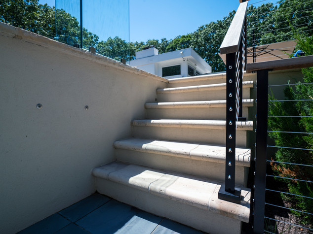Stair treads are done Techo-bloc travertine raw Ivory pavers.  Raised patio is supported by poured concrete retaining walls, finished in a beige stucco.
