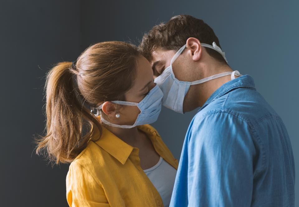 Attractive young couple getting close while wearing face masks.