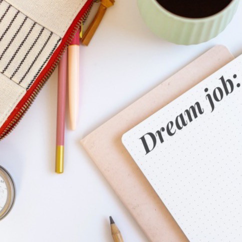 """Desktop with notepad writing out """"dream job"""""""