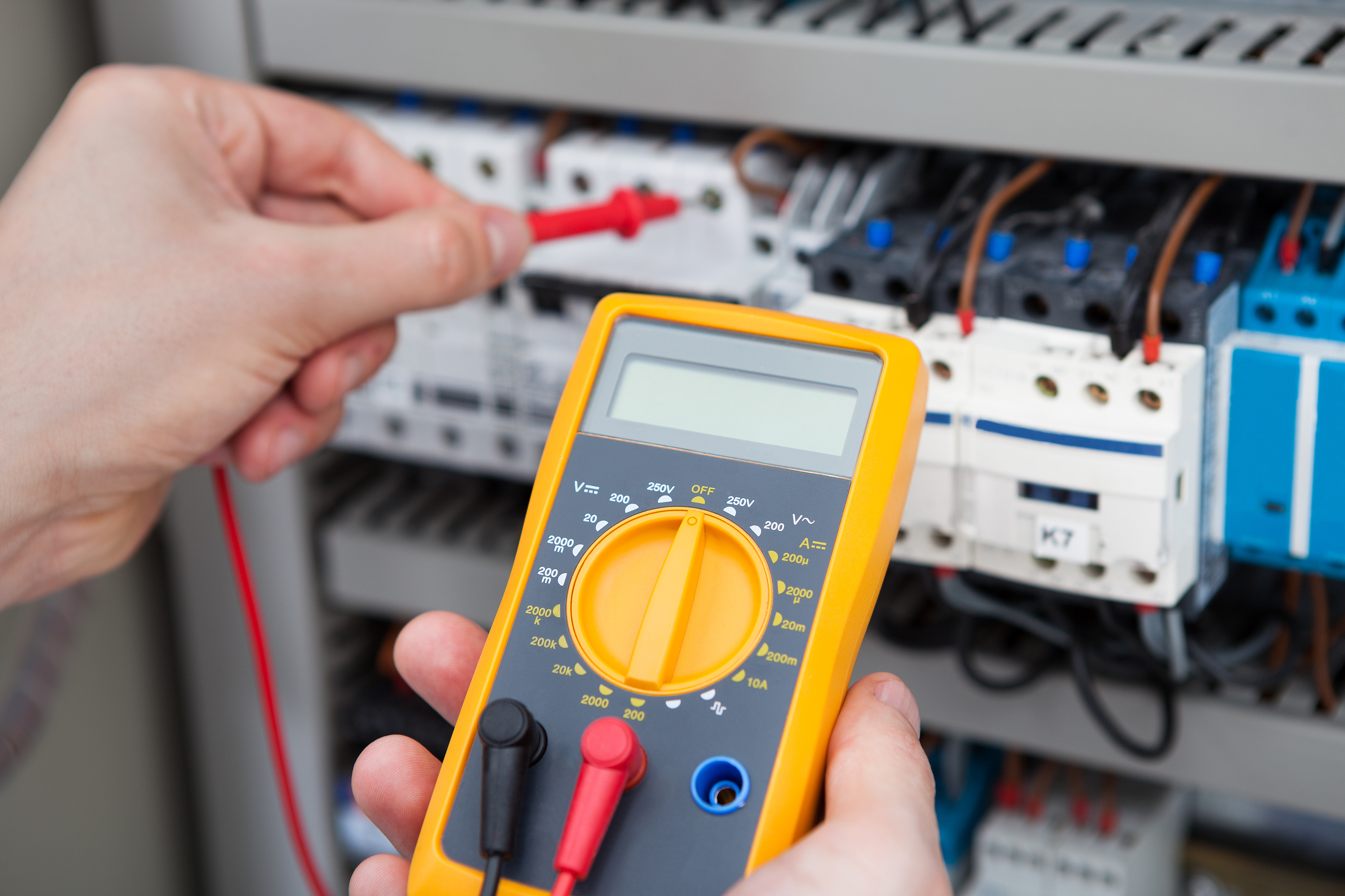 Electrician Examining Fusebox With Resistance Tester.jpg