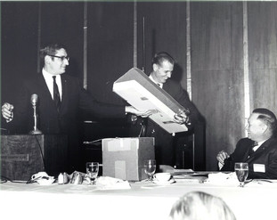 c. 1960's: Houston Alumni Chapter, Wild Game Dinner, Sagewood Country Club, Houston, late 1960s. Richard Coselli, Houston '58, (33rd HAC President), looks on as Bill Dietz shows the new shotgun he won in the door prize drawing to 44th Grand Consul Floyd Baker, Nebraska '37.