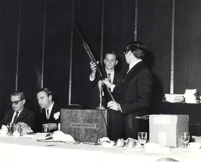 c. 1960's: Houston Alumni Chapter, Wild Game Dinner, Sagewood Country Club, Houston, late 1960s. Bill Dietz receiving the shotgun he won as a door prize from Richard Coselli, Houston '58, (33rd HAC President.) Brothers to the left are unknown.