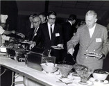 """c.1960's: Houston Alumni Chapter, Wild Game Dinner, Sagewood Country Club, Houston, late 1960s. Serving line. (L to R): Bill Knight, Houston '67 (41st HAC President), Richard Coselli, Houston '58, (33rd HAC President), and Dr. """"Red"""" Stevenson, Ohio State '22, (17th HAC President) and founder of the Wild Game Dinner."""