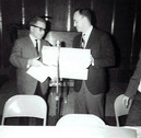 c. 1962: Houston Alumni Chapter, unidentified function, January 1962. Donald E. Walker receiving resolution and gift from Don Fullenweider.