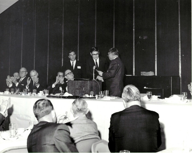 c. 1960's: Houston Alumni Chapter, Wild Game Dinner, Sagewood Country Club, Houston, late 1960s. Wild Game Dinner MC Don Martin looks on as Richard Coselli, Houston '58 (33rd HAC President)receives a Grand Consul' s citation from 44th Grand Consul Floyd Baker, Nebraska '37. Seated at the head table,( L to R), are Constantine Sig Jack Fore, Texas '22, (6th HAC President), Lloyd Anderson, Iowa '35 (24th HAC President), Grand Trustee Don Walker, Grand Praetor Milton Jackson.