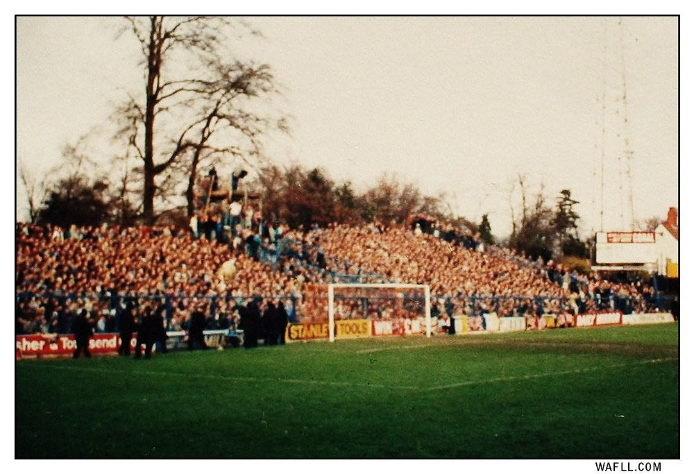 Leeds fan pack the away end at Oxford hanging perilously to the MOTD scaffold and perimeter fencing. The scoreboard is under the floodlight.