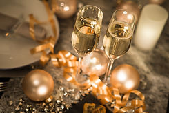 new years eve party table with champagne flute ribbon and golden glitter .jpg