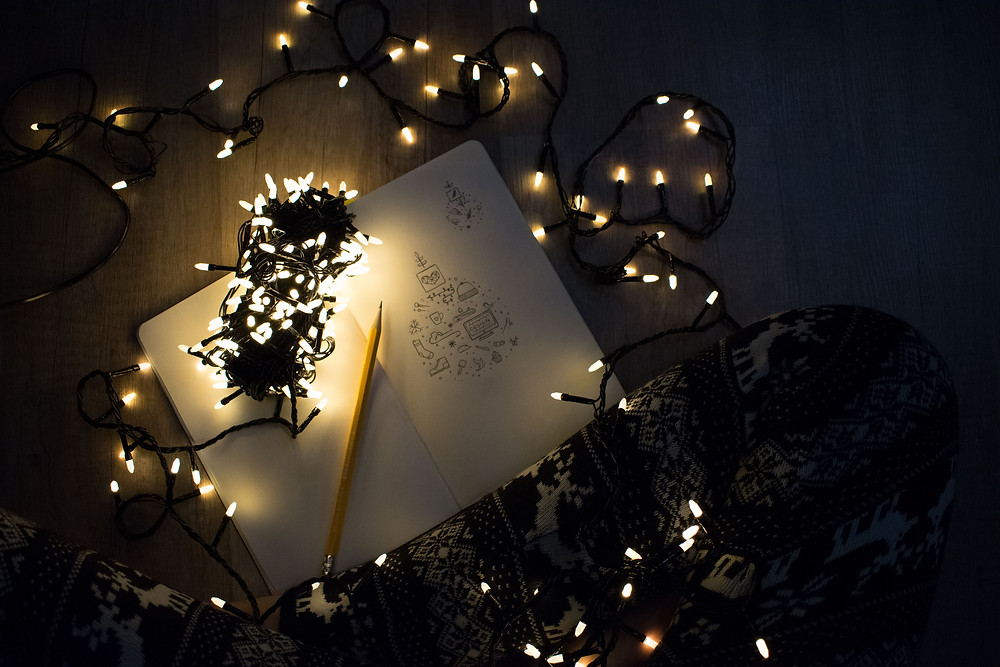 Notebook with pencil sketches lit by fairy lights