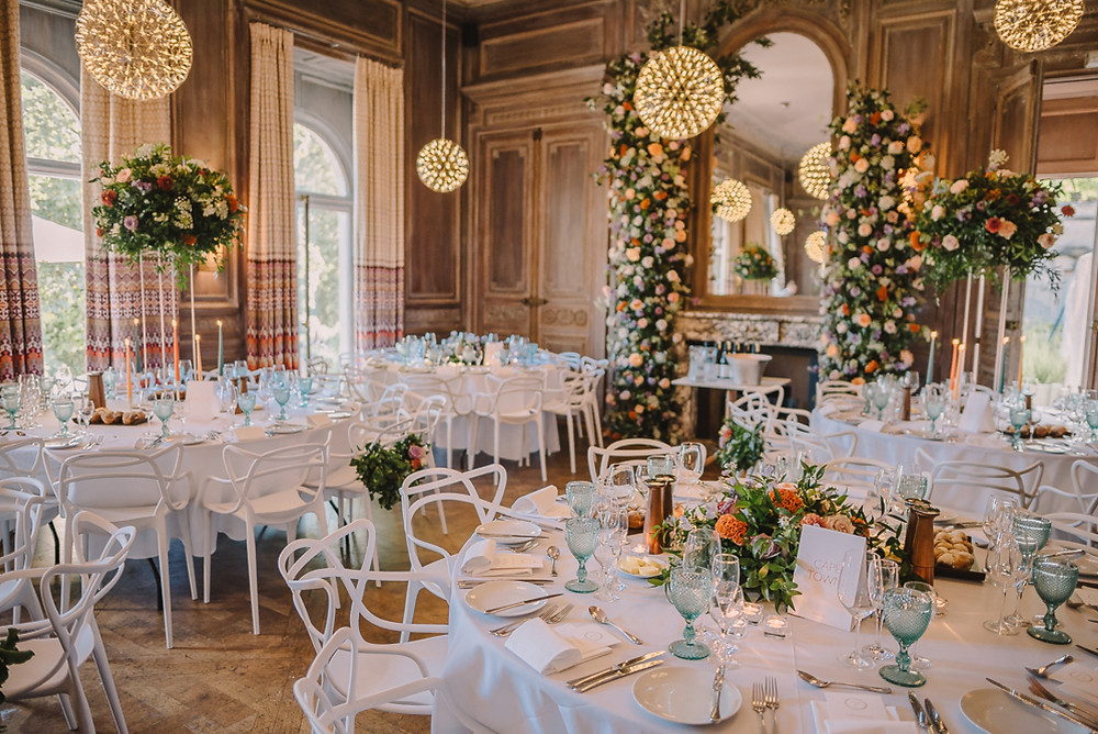 Dining room at Cowley Manor with floating geometric lights and large floral arrangements in lilac and orange
