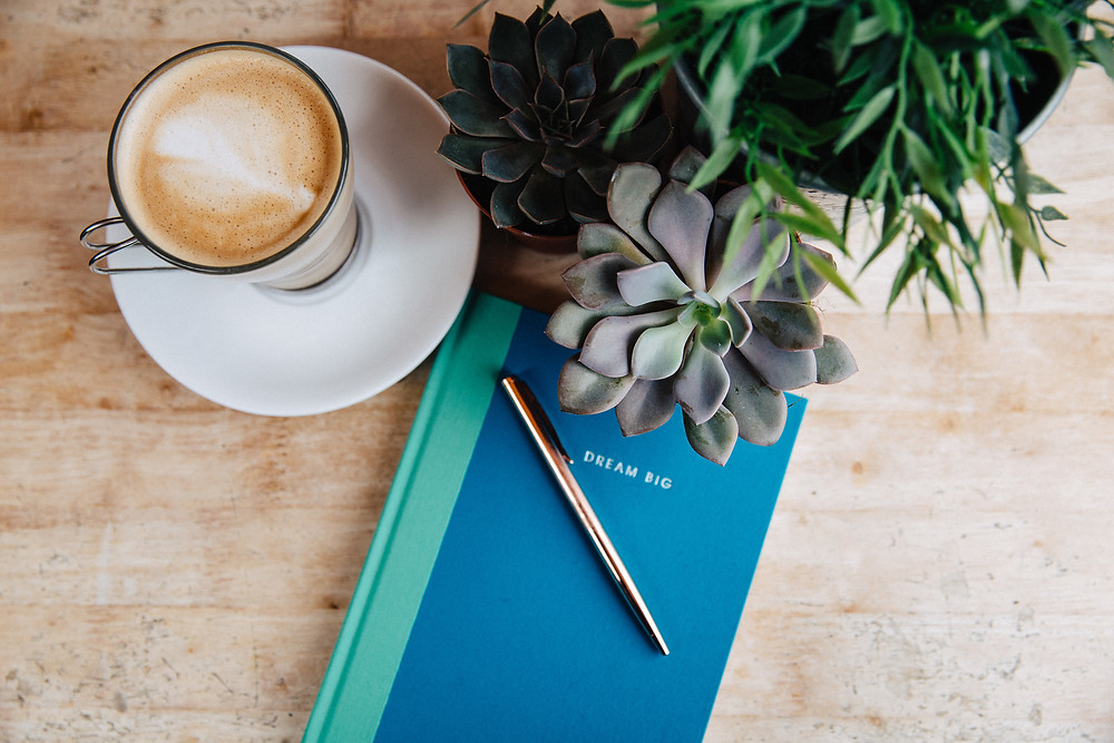 Flatlay of blue notebook and gold pen with coffee and succulents