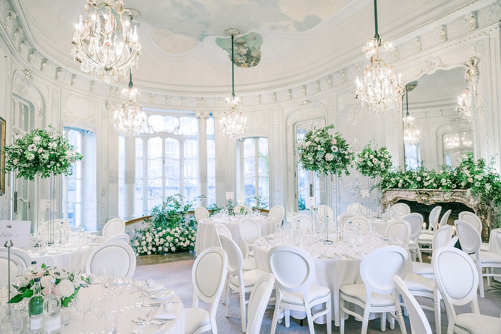 All white wedding at The Savile Club. Large fireplace floral installation and wild arrangement of white roses behind the top table. Structured high white floral centrepieces.