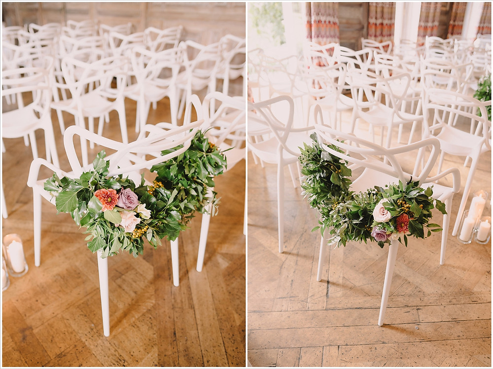White masters chairs adorned with flowers at Cowley Manor