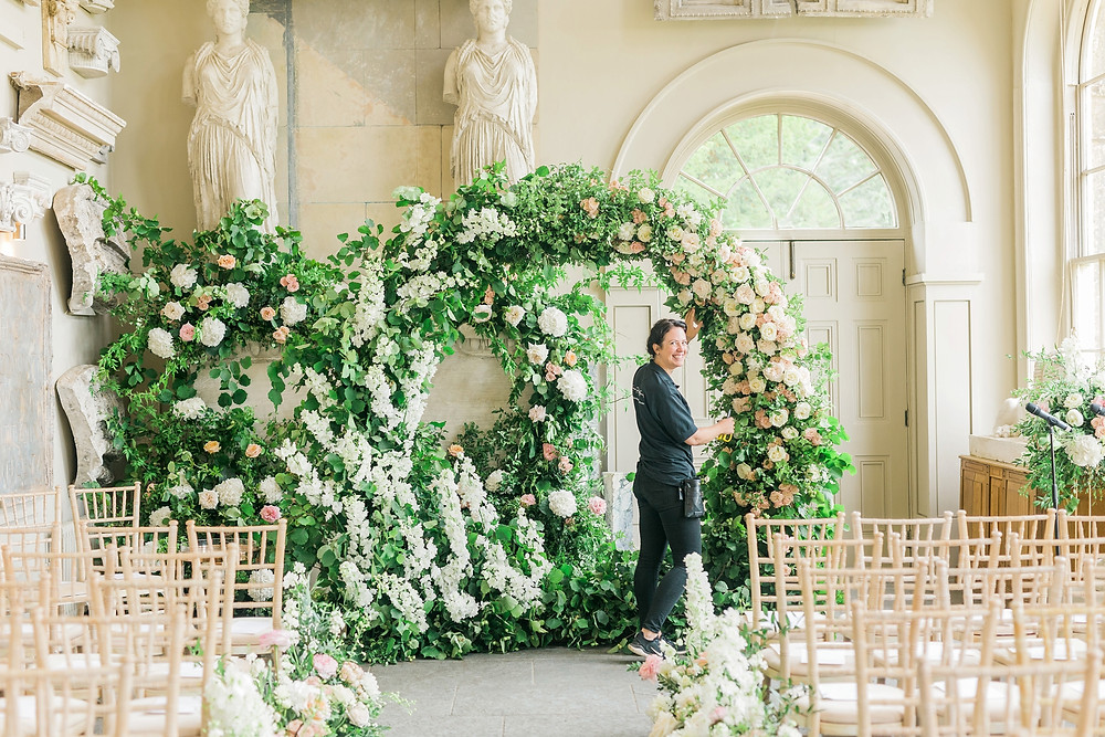 Elaborate floral infinity symbol arch with roses and delphiniums at Aynhoe Park
