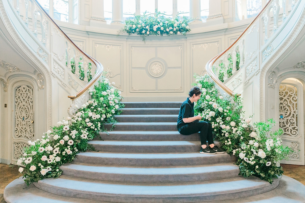 Luxury florist Emma Soulsby putting the finishing touches to an enormous staircase installation