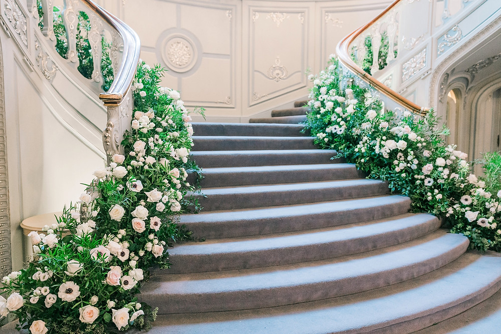 Luxury white floral staircase installation by Emma Soulsby Flowers. Featuring white roses, anemones and orchids