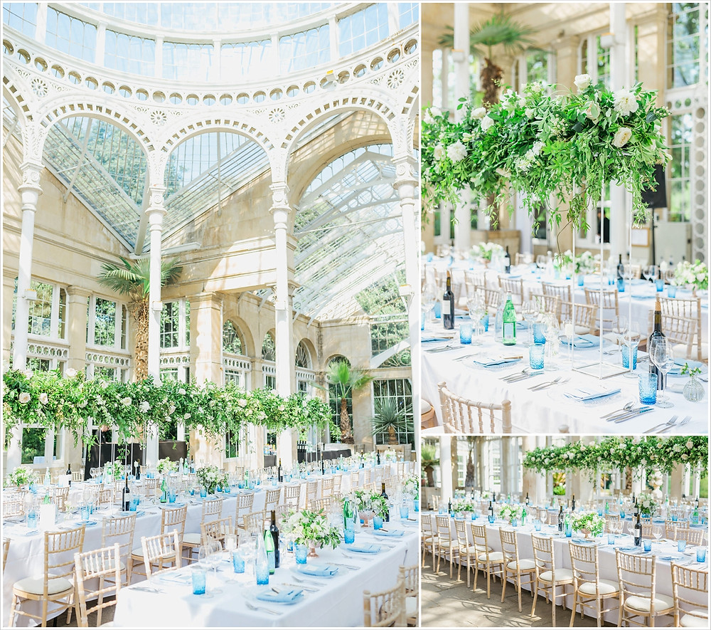 The finished tablescapes in the Great Conservatory at Syon Park. Statement hanging flowers in green and white, pale blue glassware and gold accents.