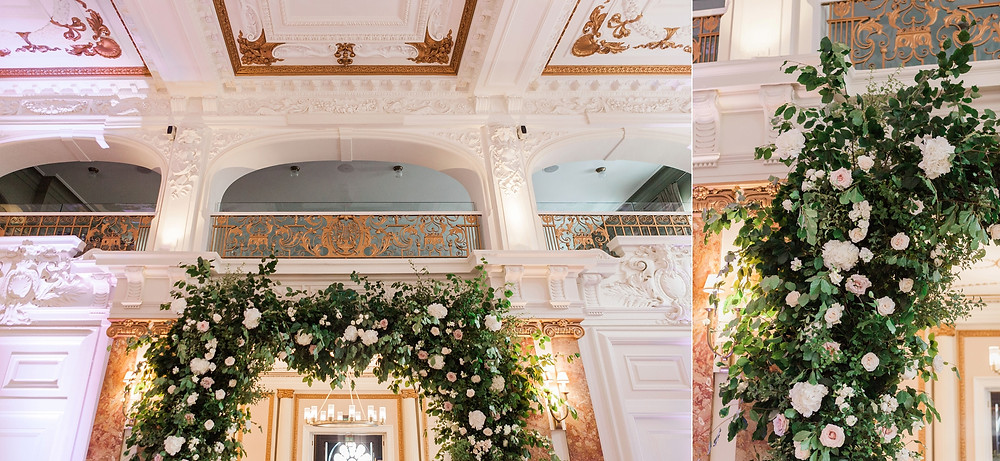 large floral arch in the ballroom of the Kimpton Fitzroy. Deep green foliage, white and pale pink roses, hydrangeas, dahlias and stocks