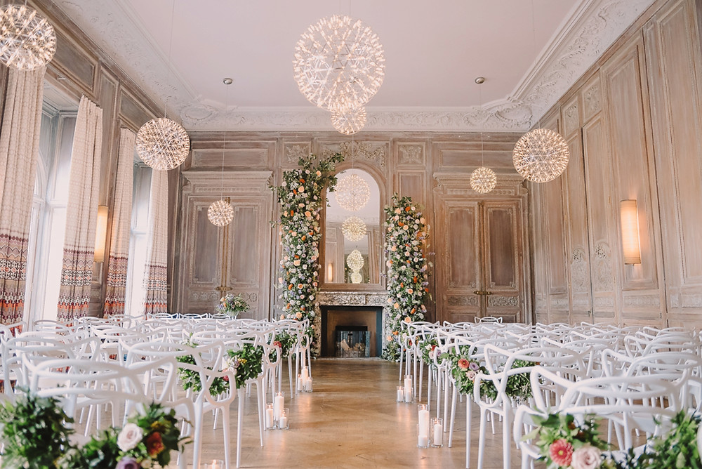 Ceremony set up with masters chairs and large floral arch at Cowley Manor